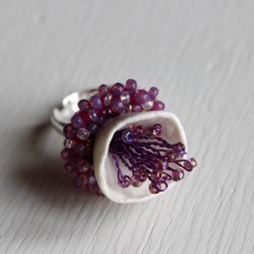 bague porcelaine blanche clochette, inspiration anémone, pistils et bxtérieur broderie de perles mauves, montée sur anneau réglable en argent