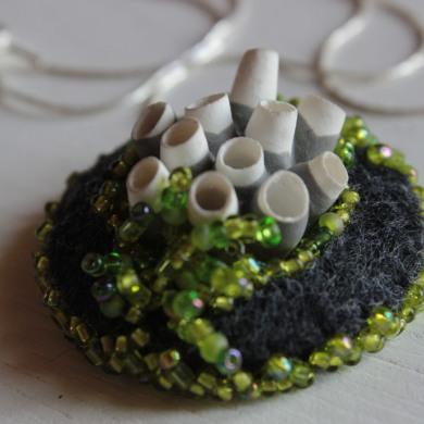 collier porcelaine blanche inspiration corail sur feutre gris, brodé de perles vertes, sur chaine en argent