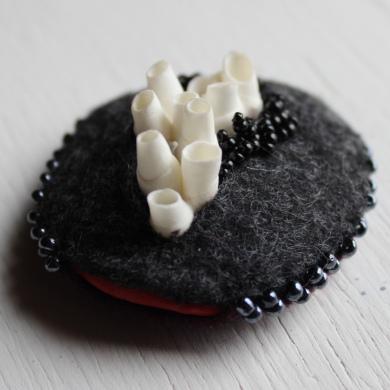 broche inspiration corail et rocher, une pièce de porcelaine enfermée entre deux pièces de feutre gris anthracite, dont émergent des alvéoles en tubes de porcelaine blanche et sur le côté un peu de porcelaine rouge apparait, parsemé de broderie de perles